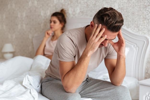 Trieste man zittend op bed met zijn vriendin