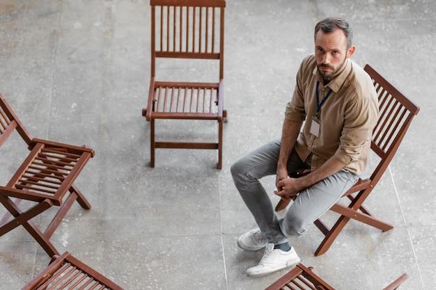 Trieste man zittend op stoel volledig schot