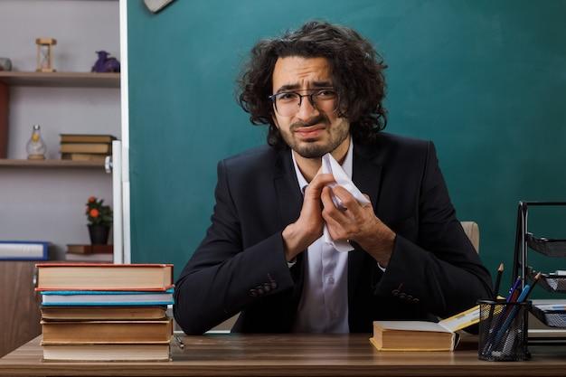 Trieste mannelijke leraar met een bril die papier verplettert aan tafel met schoolhulpmiddelen in de klas