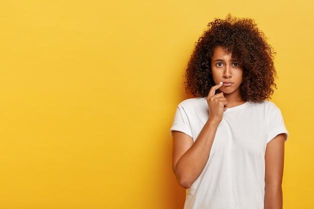 Trieste mokkend afro-amerikaanse millennial vrouw, houdt wijsvinger in de buurt van koren van lippen, beledigd door iemand, voelt zich teleurgesteld, gekleed in vrijetijdskleding, poseert tegen gele muur, heeft een probleem