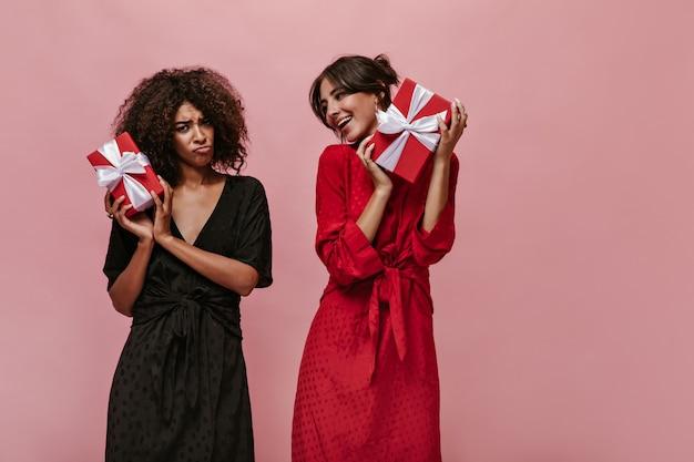 Trieste mulatvrouw in donkere outfit die in de camera kijkt, een rode geschenkdoos vasthoudt en poseert met een gelukkig meisje in lichte kleding