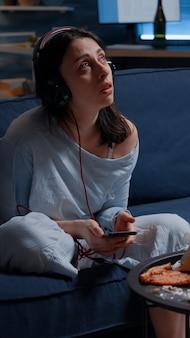 Trieste nadenkende angstige vrouw die muziek luistert met smartphone, zich eenzaam voelt bezorgd over...