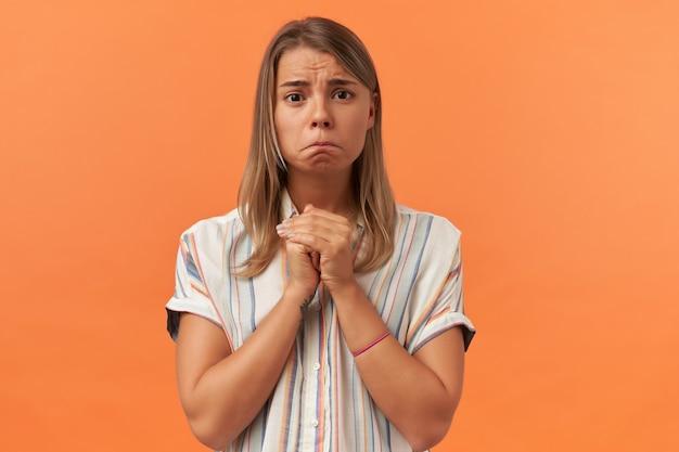 Trieste ongelukkige jonge vrouw in vrijetijdskleding houdt handen in gebedspositie en kijkt naar de voorkant geïsoleerd over oranje muur