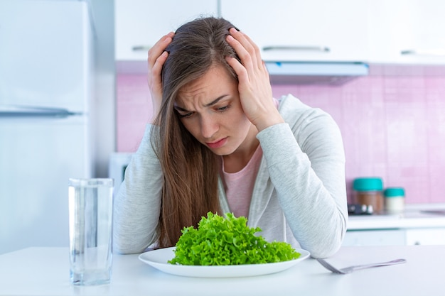 Trieste ongelukkige vrouw is moe van een dieet en wil geen organisch, schoon gezond dieetvoedsel eten