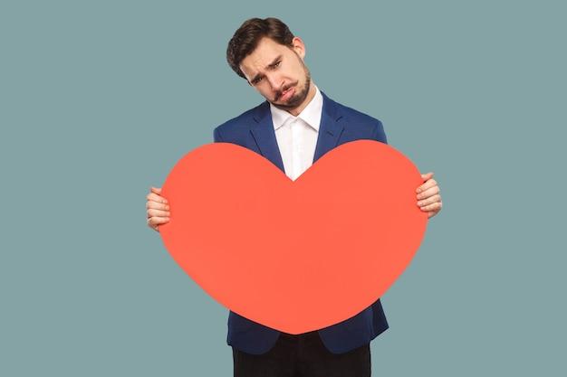 Trieste ongelukkige zakenman in blauwe jas en wit overhemd die staat en rode grote hartvorm vasthoudt en naar de camera kijkt met huilen en gebroken hart. binnen, studio-opname geïsoleerd op lichtblauwe achtergrond.
