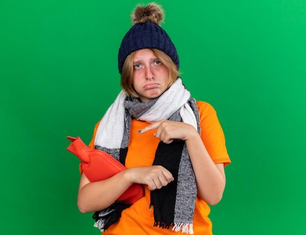 Trieste ongezonde jonge vrouw in oranje t-shirt met hoed en warme sjaal om nek voelt zich verschrikkelijk met warmwaterkruik wijzend met de vinger erop die lijdt aan kou die over groene muur staat