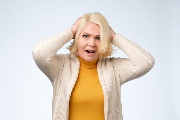 Trieste oude senior vrouw naar beneden te kijken en te huilen