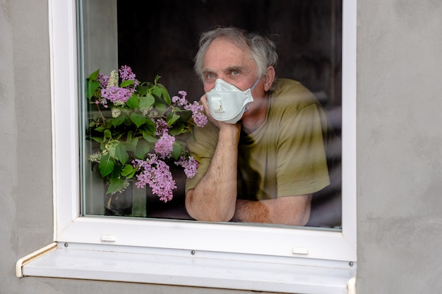 Trieste oudere man in een beschermend masker kijkt uit het raam, wachtend op het einde van de zelfisolatie. concept van coronavirus quarantaine thuis blijven en sociale afstand.