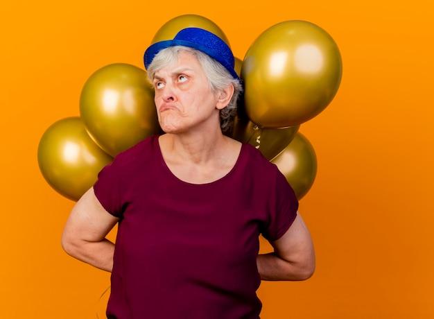 Trieste oudere vrouw met feestmuts houdt helium ballonnen achter opzoeken op oranje