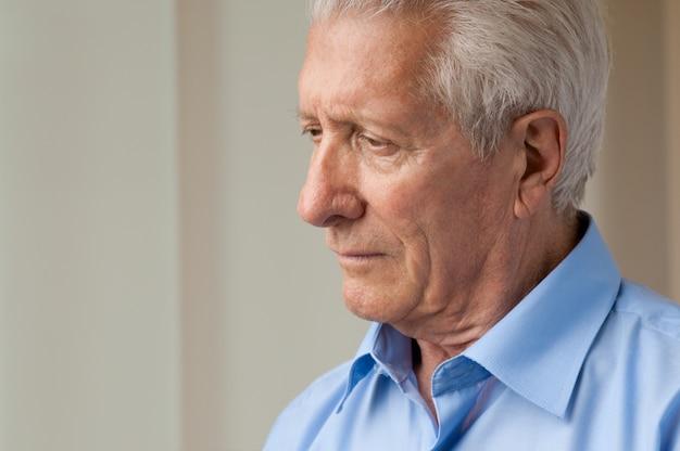 Trieste senior man naar beneden te kijken met angst