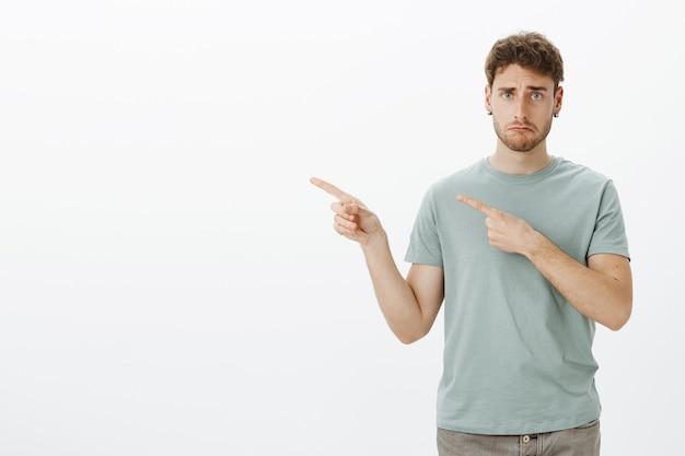 Trieste sombere jongeman in t-shirt, boos teleurgesteld gezicht terwijl hij met wijsvingers naar links wijst, fronsend, ongelukkig en ellendig