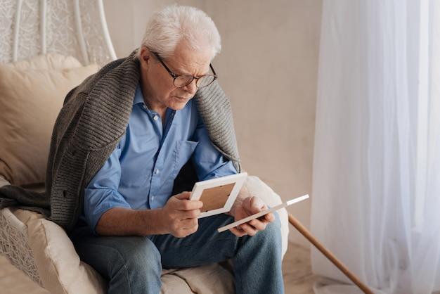 Trieste sombere ongelukkige man zittend in de fauteuil en met oude foto's terwijl hij zich zijn jeugd herinnert