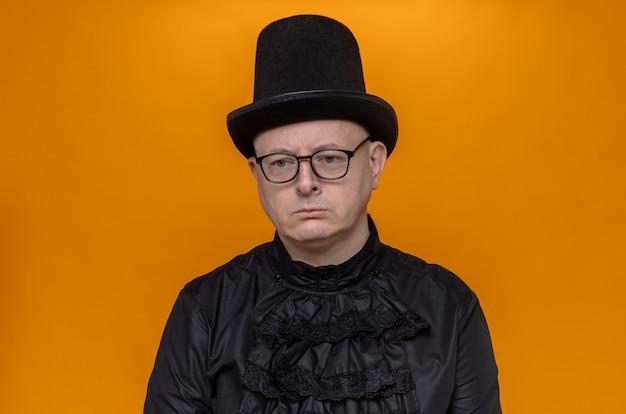 Trieste volwassen man met hoge hoed en bril in zwart gotisch shirt kijkend naar de zijkant
