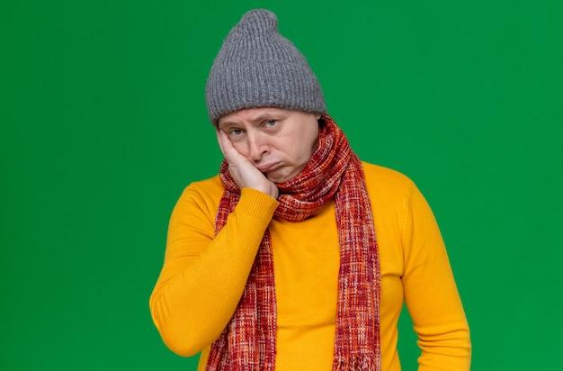 Trieste volwassen man met wintermuts en sjaal om zijn nek die hand op zijn gezicht legt en kijkt