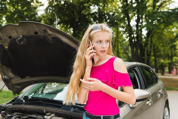 Trieste vrouw in stress met mobiele telefoon in de buurt van auto
