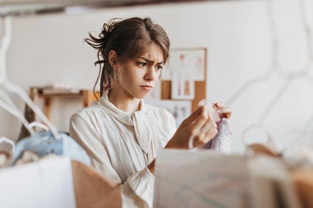 Trieste vrouw kijkt naar kantmonster van gietkwaliteit