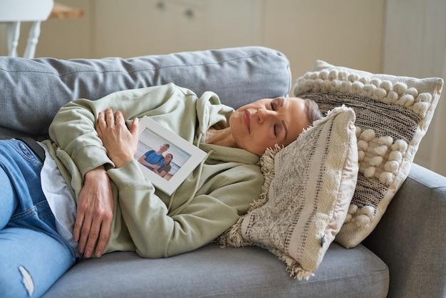 Trieste vrouw van middelbare leeftijd met familiefoto met haar kinderen in frame die ogen dicht houden en dromen dream