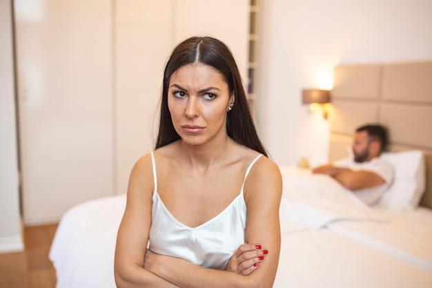 Trieste vrouw zit aan de rand van bed voor man