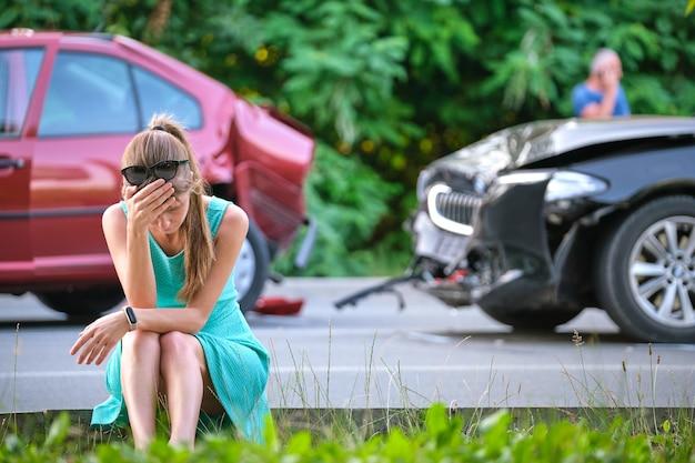 Trieste vrouwelijke bestuurder zittend aan straatkant geschokt na auto-ongeluk. verkeersveiligheid en voertuigverzekering concept.