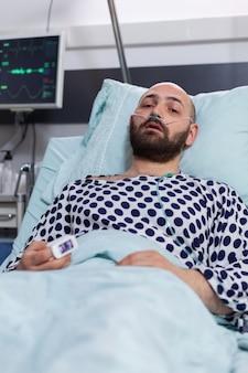Trieste zieke man met een zuurstofslang in de neus die in de camera rust tijdens het respiratoire herstel op de ziekenhuisafdeling