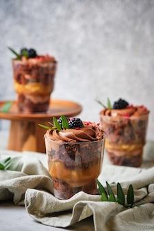 Trifles gemaakt van chocoladebiscuit met karamel-pinda vulling. het dessert is versierd met romige chocoladekaasroom, verse bramen, gevriesdroogde frambozen en groene bladeren.
