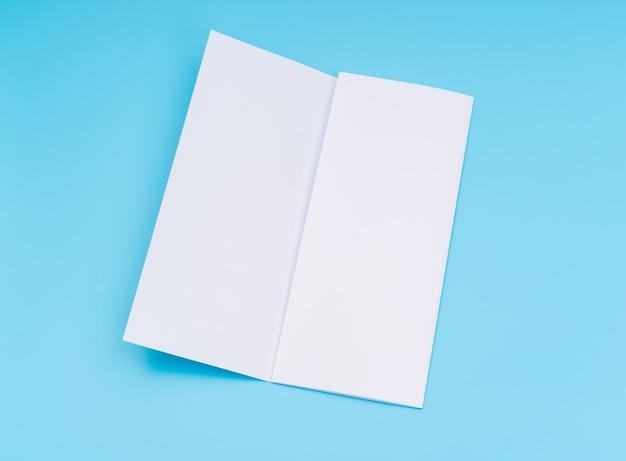 Trifold wit sjabloon papier op blauwe achtergrond.