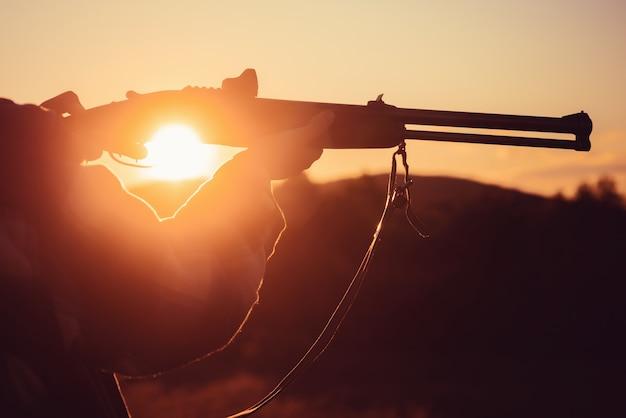 Trigger van de jachtgeweergeweerjager gesilhouetteerd in het prachtige zonsondergangsilhouet van de jager