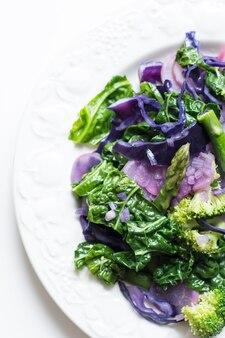 Trillend kleurrijk schot van gekookte de lente seizoengebonden groenten op een witte achtergrond
