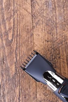 Trimmer met mondstukken. een nieuwe draadloze trimmer kopen. op een houten achtergrond. detailopname. met ruimte voor tekst