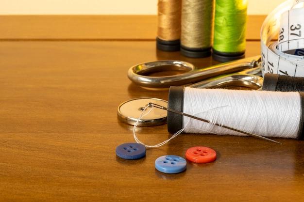 Trims naaien. spoel van draad, naald, knopen, schaar en meetlint.