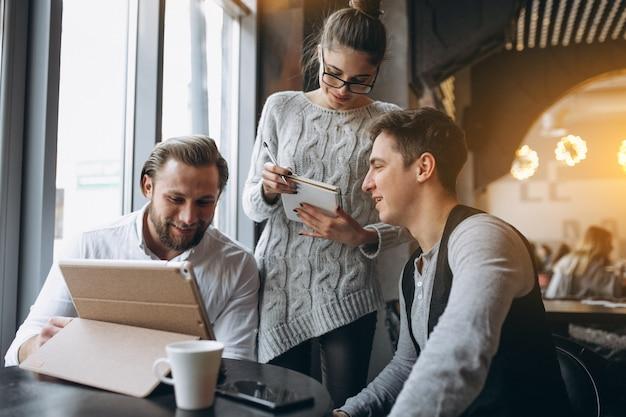Trio mensen die aan een project op een tablet in een koffie werken