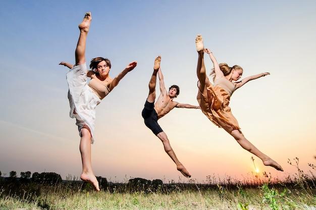 Trio van yang-balletdansers treden buiten op zonsondergang op.
