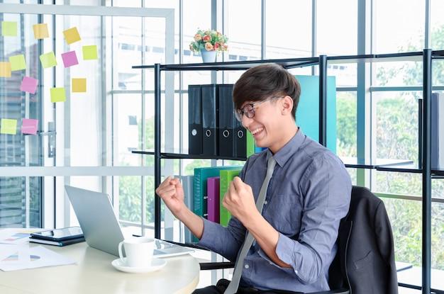 Triomfantelijk portret van jonge aziatische zakenman en vier met wapens omhoog voor baissucces in bureau