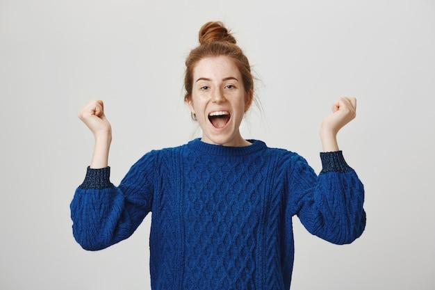 Triomfantelijk schattig roodharig meisje viert prestatie, schreeuwend ja