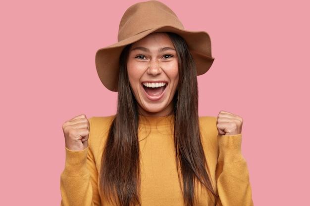 Triomfantelijke aantrekkelijke vrouwelijke collega schreeuwt van geluk, roept ja uit als behaalde geweldige resultaten, steekt gebalde vuisten op, viert de overwinning