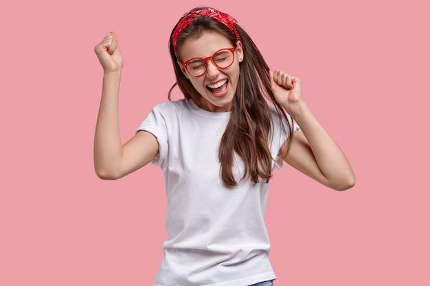 Triomfantelijke blije vrouw balde vuisten, verheugt zich op positief nieuws, roept blij uit, modellen over roze ruimte