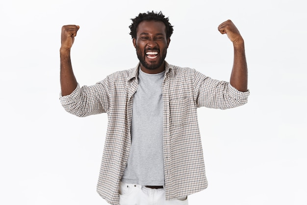 Triomfantelijke gelukkige afro-amerikaanse bebaarde man die zich kampioen voelt