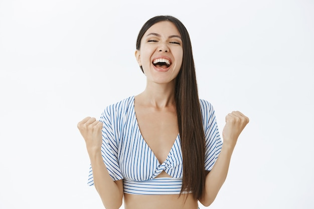 Triomfantelijke gelukkige en opgetogen jonge, succesvolle en gelukkige vrouw in bijgesneden top die schreeuwt van vreugde