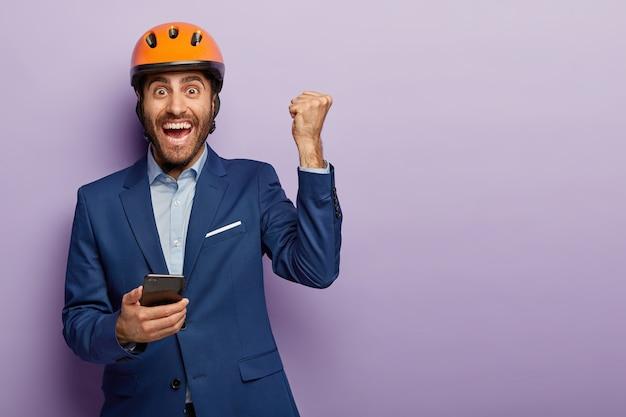 Triomfantelijke gelukkige ingenieur houdt mobiele telefoon vast, steekt gebalde vuist op, gebruikt telefoon, verheugt zich op de bouwplaats, draagt een formeel pak en een oranje helm. jonge architect krijgt bericht op mobiel