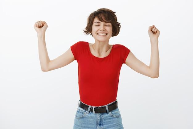 Triomfantelijke gelukkige vrouw die handen in hoera opheft, verheugt zich gebaar, overwinning viert