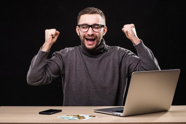 Triomfantelijke kantoormedewerker slaagde erin om online een goede deal te sluiten. winnaar man aan tafel met laptop, telefoon en geld met bitcoin