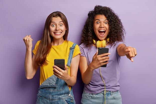 Triomfantelijke vriendinnen poseren met hun telefoons