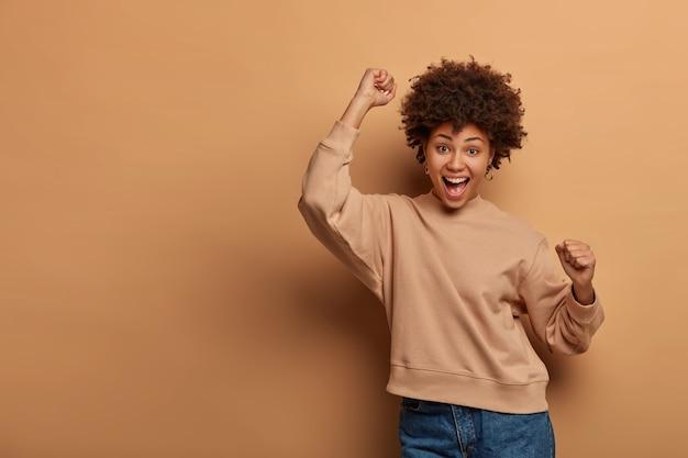 Triomfantelijke, vrolijke vrouw viert de overwinning, voelt zich gelukkig en opgewekt