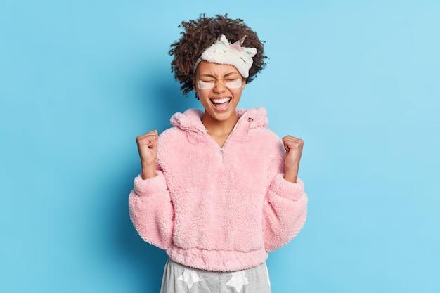 Triomfantelijke vrouw met krullend haar balt vuisten van vreugde gekleed in pyjama verheugt zich op succesvolle dag bereidt zich voor op slaap geïsoleerd over blauwe muur
