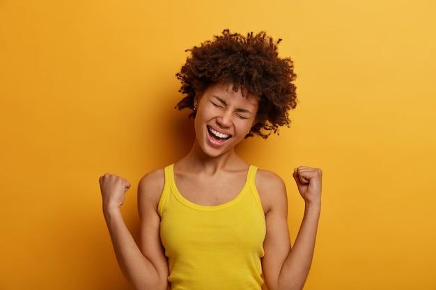Triomfantelijke vrouw verheugt zich op de winnende wedstrijd, kantelt het hoofd en lacht positief uit