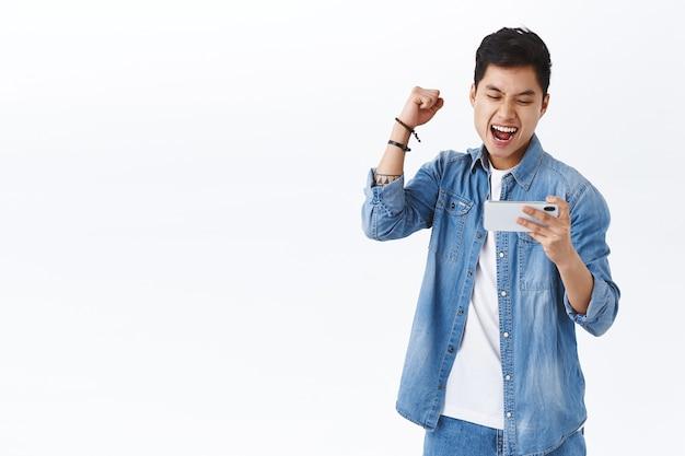 Triomferende aziatische vreugdevolle man die wint in het spel, vuist opheft om te vieren en ja zegt, hoera, tevreden glimlachend op mobiele telefoon, eerste niveau geëindigd