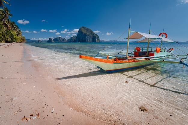Trip banca boot op zandstrand van een tropisch eiland. el nido, palawan, filippijnen.