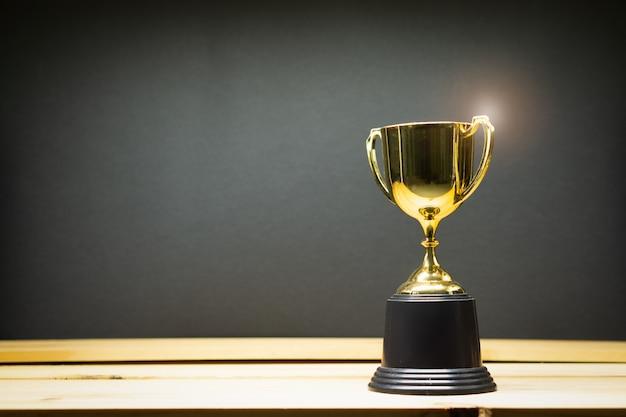 Trofee op de top van oude houten tafel voor blackboard.