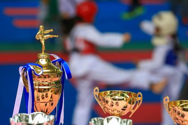 Trofee voor taekwondo-wedstrijd met atleten die op de achtergrond vechten