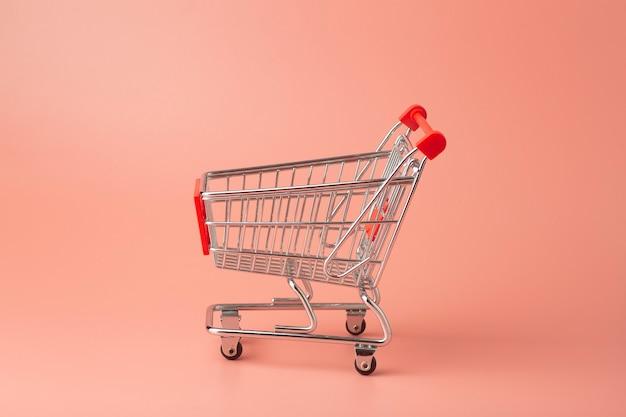 Trolley uit de supermarkt minimaal op een gekleurde achtergrond. verkoop en aankopen concept.